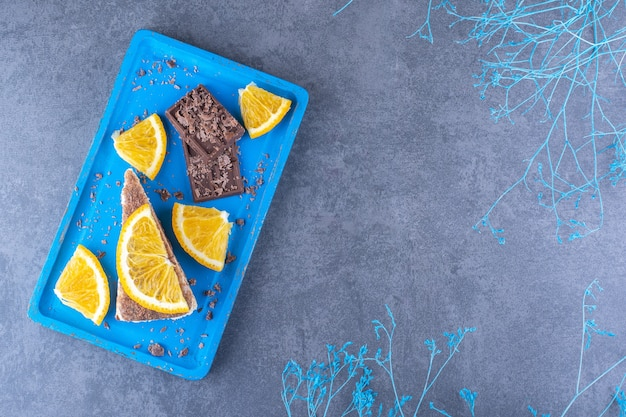 Blue platter next to decorative branches, with a cake slice, chocolate plates and orange slices on marble surface