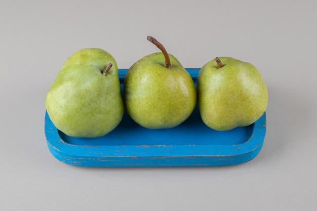 大理石の上に一握りの梨と青い大皿