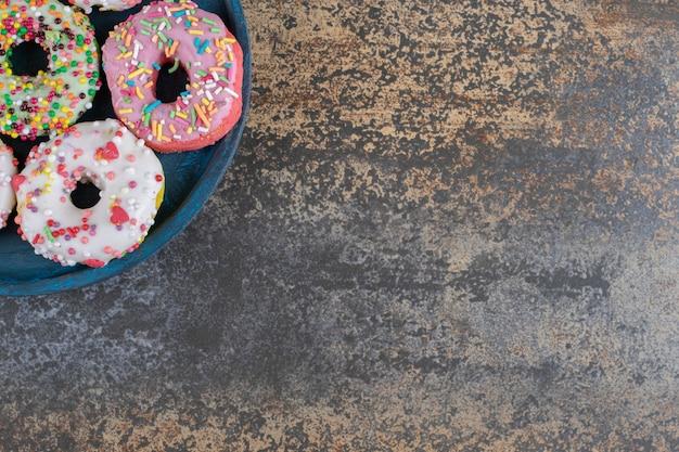 Синее блюдо с пончиками, посыпанными конфетами на деревянной поверхности