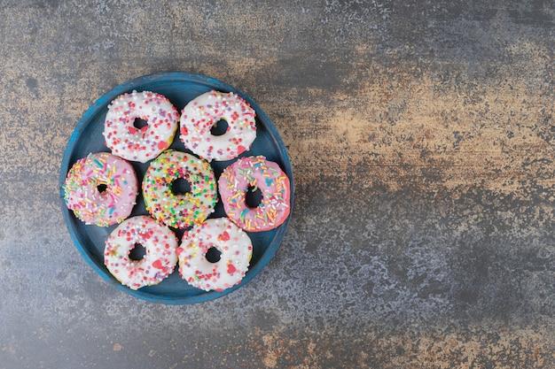 Синее блюдо с пончиками, посыпанными конфетами на деревянной поверхности Бесплатные Фотографии