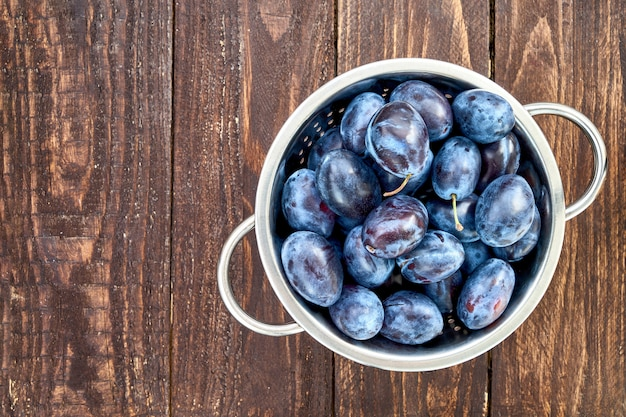 Blue plums in rustic colander on old wooden table. organic food.