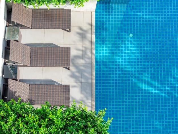 푸른 수영장과 나무 빈 녹색 나무 근처 선베드를 짜다