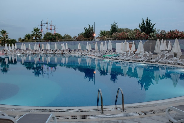 호텔 터키 관광 개념의 우산과 선베드가 있는 파란색 수영장