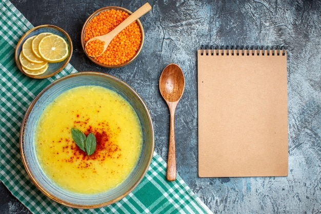A blue pot with tasty soup served with mint and pepper next to chopped lemon wooden spoon and yellow pea spiral notebook on blue background