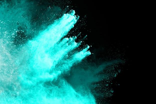 黒の背景に青い粉の爆発。フリーズモーション。