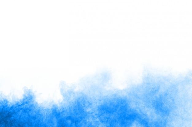 Взрыв голубого порошка на белой предпосылке. цветное облако. разноцветная пыль взрывается. краска холи.