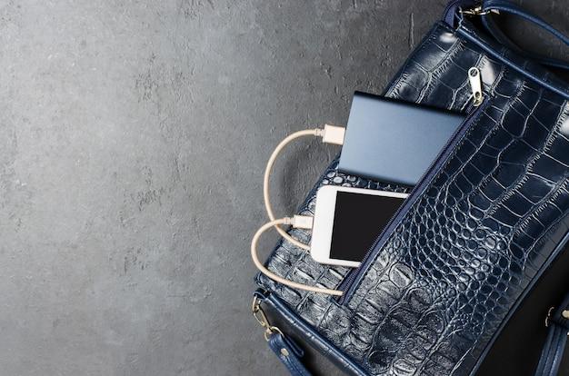 Blue power bank и телефон в женской сумке. темно-серый бетонный фон. копировать пространство