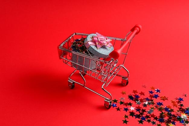 쇼핑 카트에 분홍색 활이 있는 파란색 선물 상자와 빨간색 배경에 색종이 조각이 있습니다.