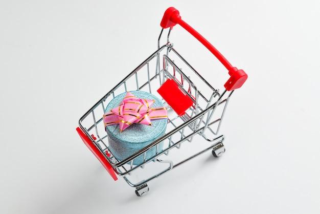 흰색에 장바구니에 분홍색 나비와 함께 파란색 선물 상자