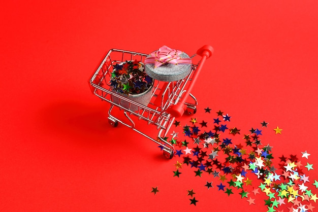 Blue present box with pink bow in a shopping cart and confetti on a red background.