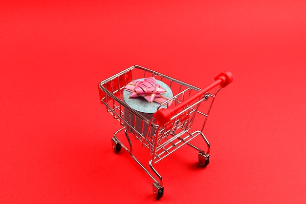 Blue present box with pink bow in a shopping cart on a red background.