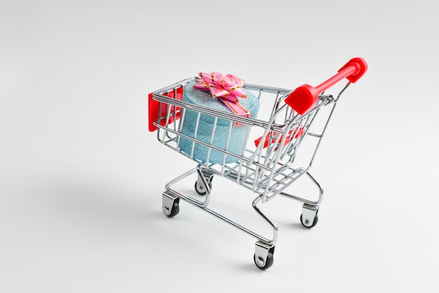 Blue present box with pink bow in a shopping cart on a white background.