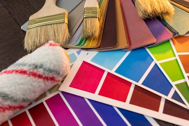 木の板の家の修理または改修のためのカラーパレットとペイントブラシ付きの青い保護手袋。機器のセット