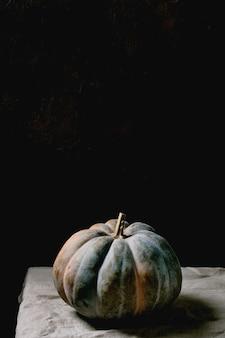 리넨 식탁보에 파란 호박입니다. 어두운 정물화. 가을 수확. 복사 공간