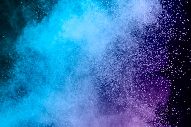Blue and purple dust of powder on dark background