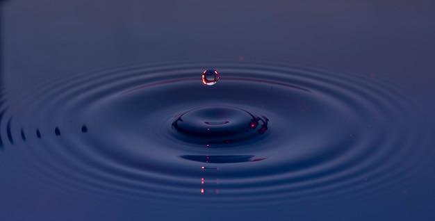 Blue and purple water drops suspended in the air and forming waves on the liquid surface