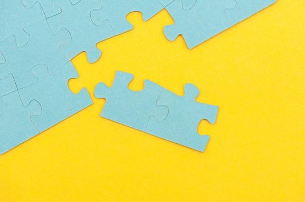 黄色の背景に欠けている部分と青いパズルの背景上からの眺め