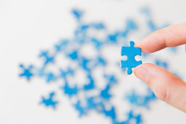Blue puzzle in hand. hand holding puzzle piece on white background. connecting piece jigsaw puzzle, business connection, education, society and teamwork