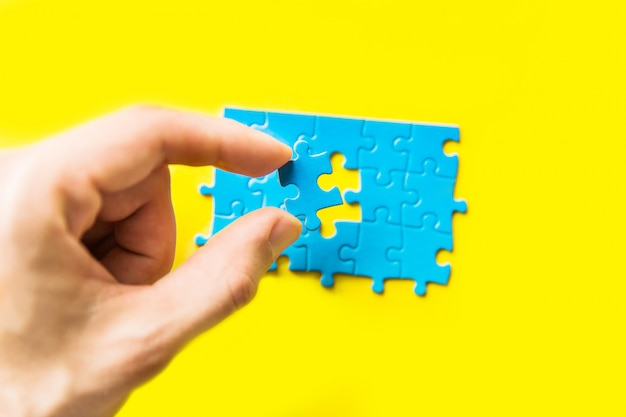 노란색 배경에 손에 퍼즐 블루. 손을 잡고 퍼즐 조각입니다.