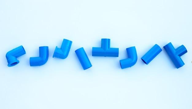 Голубое соединение трубы пвх изолированное на белой стене.