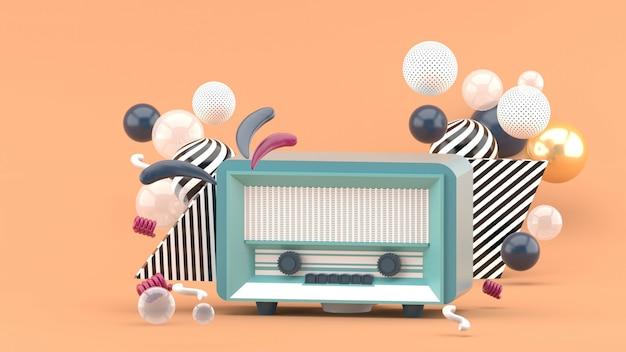 茶色のカラフルなボールに囲まれた青いラジオ。 3dレンダー