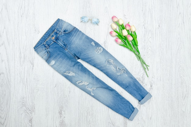 Blue ragged jeans and bouquet of tulips. fashionable concept
