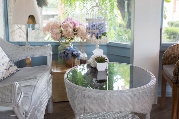 Голубая софа ротанга с подушкой в живущей комнате около окна с видом на сад в современном доме.