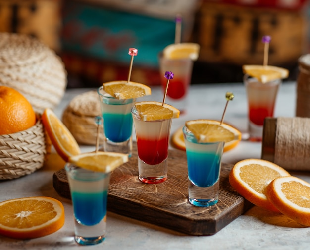 Blue and red alcohol drinks with orange slices.