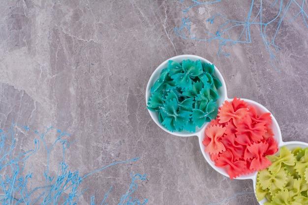 Синие, красные и зеленые сырые пасты в тройных белых чашках