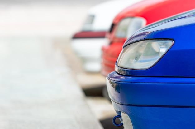 파란색, 빨간색과 흰색 차가 거리에 연속 주차되어 있습니다.