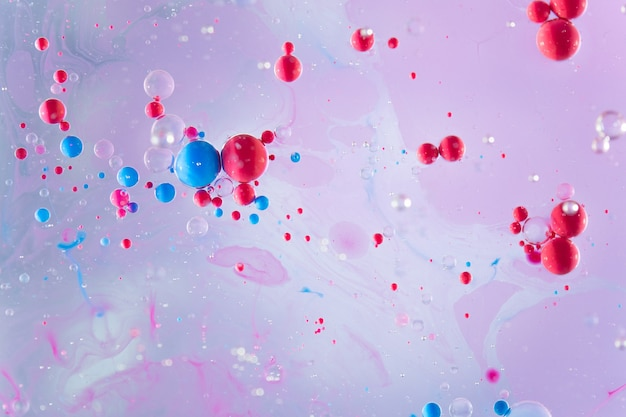 Blue and red color bubbles and oil in water colorful abstract background.