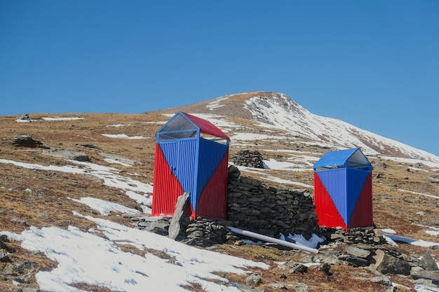 Blue and red color restroom. sanitary toilet cabin in the snow covered mountain.