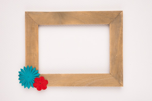 Blue and red flower on the corner of wooden empty frame isolated on white backdrop