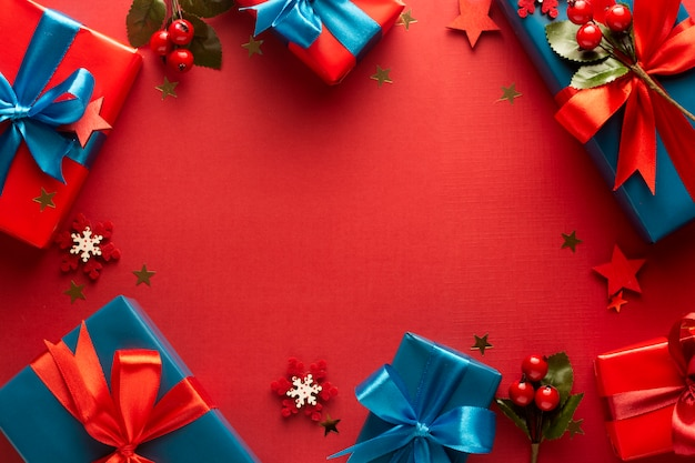 Blue and red gift boxes with red ribbon and bow isolated on red surface, frame background in top view,