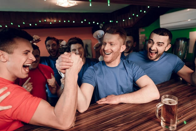 Blue and red team fans arm wrestling at sports bar
