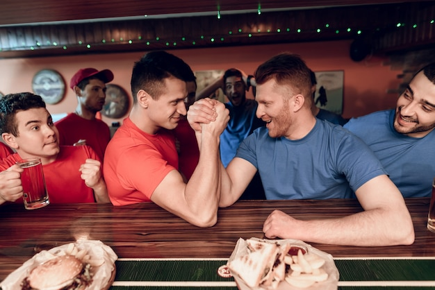 Blue and red team fans arm wrestling in sports bar