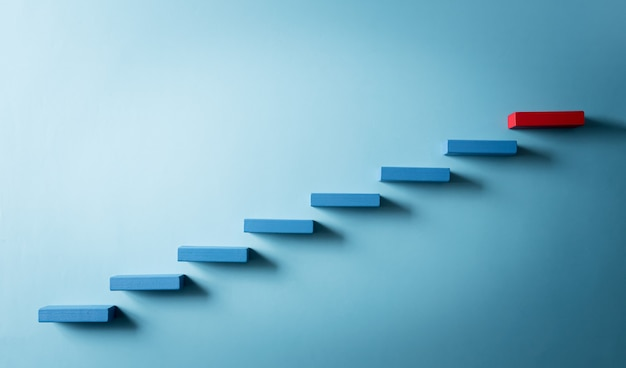 Blue and red wooden block stacking as step stair success in business growth concept