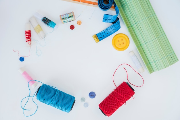 Blue and red yarn; spools; button; measuring tape and placemat on white background