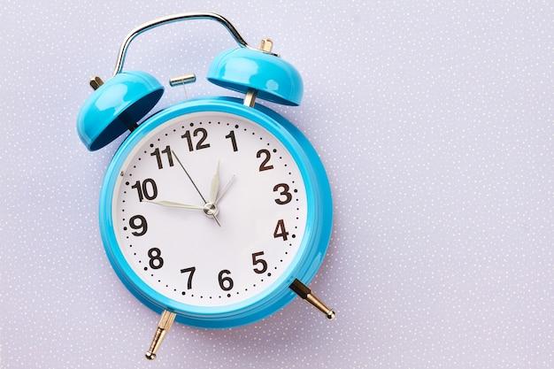 Синий ретро будильник на зимнем фоне.