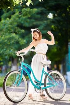 여름 햇빛에 아름 다운 여자 근처 블루 복고풍 자전거