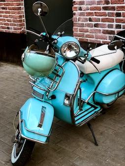 Синий ретро-скутер со шлемом, висящим на рулевом колесе на улице