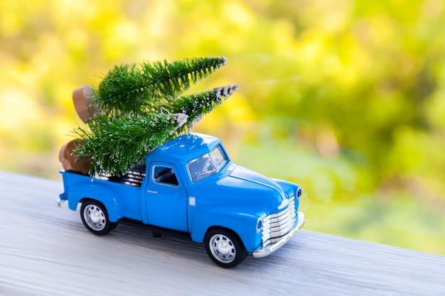 白で隔離、クリスマスや新年の贈り物を提供する青いレトロなおもちゃの車