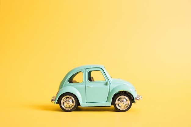 Blue retro toy car on yellow. summer travel concept. taxi
