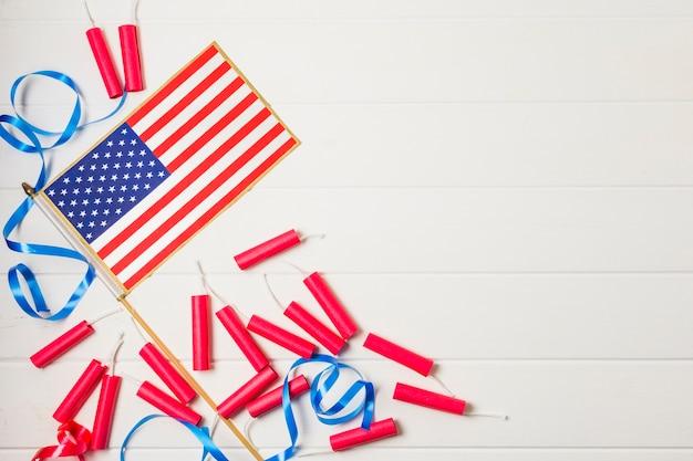 青いリボンと白い板の背景にアメリカ国旗と赤い爆竹