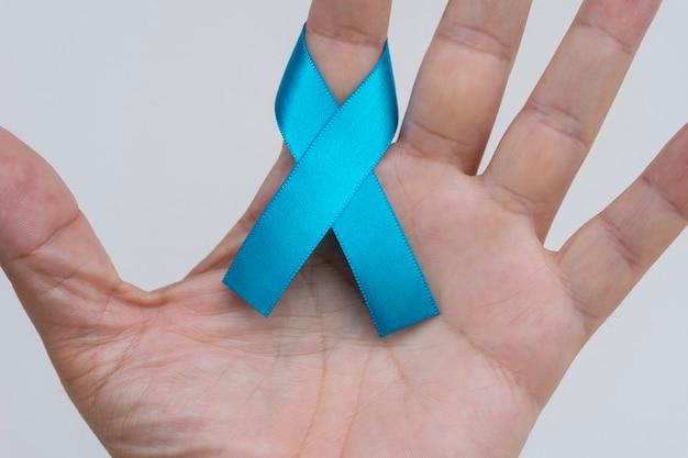 손가락에 블루 리본 활입니다. 전립선암 예방 캠페인. 푸른 11월