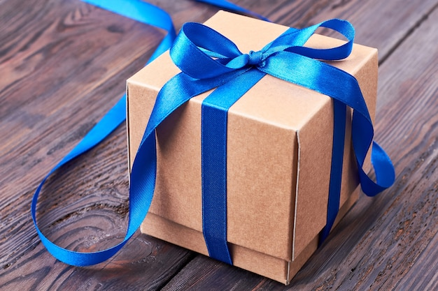 贈り物に青いリボンの弓。木の表面にプレゼントボックス。弓の作り方。