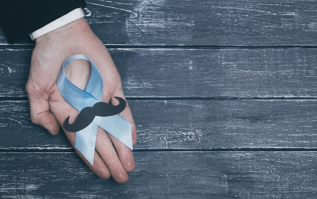 Blue ribbon in the hand of a man. symbol of prostate cancer. awareness of the problem. cop