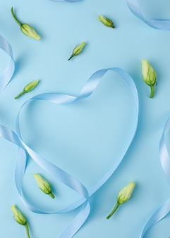 Blue ribbon in a heart shape with flower buds.