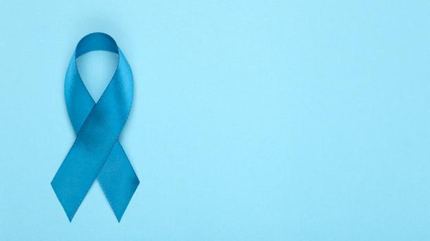 背景にブルーのリボン。前立腺がん啓発月間。世界の前立腺癌の月とヘルスケアの概念の青いリボンのシンボル。コピースペース