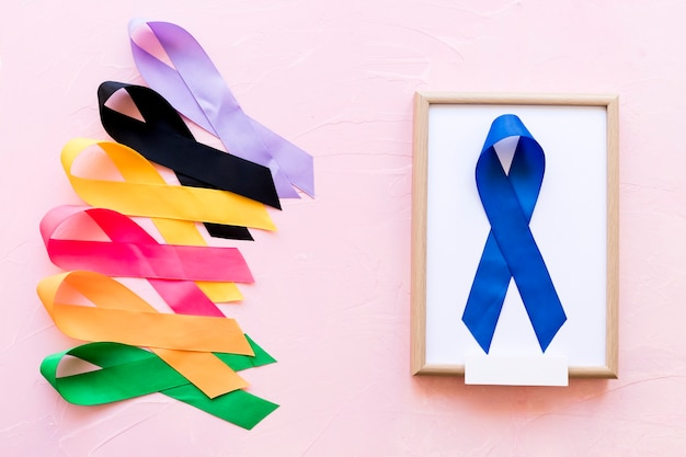 Blue ribbon on white wooden frame near the row of colorful awareness ribbon